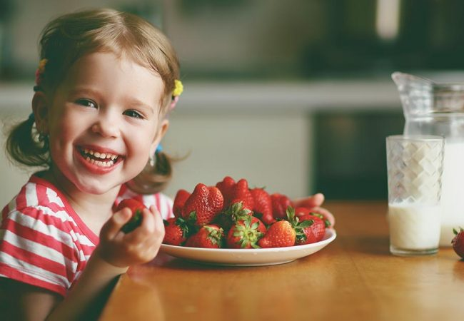 A young girl having a healthy snack of strawberries and milk