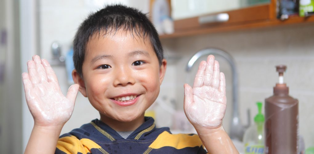 Young boy smiles and shows his hands as he is washing them