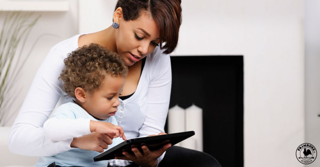 A mother teaching her young son with the help of a tablet