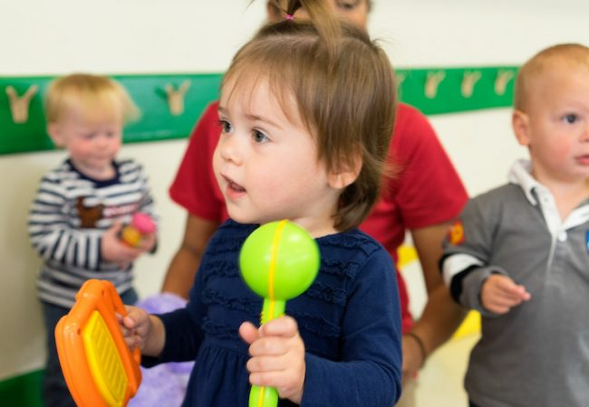 Primrose student plays with maracas in classroom