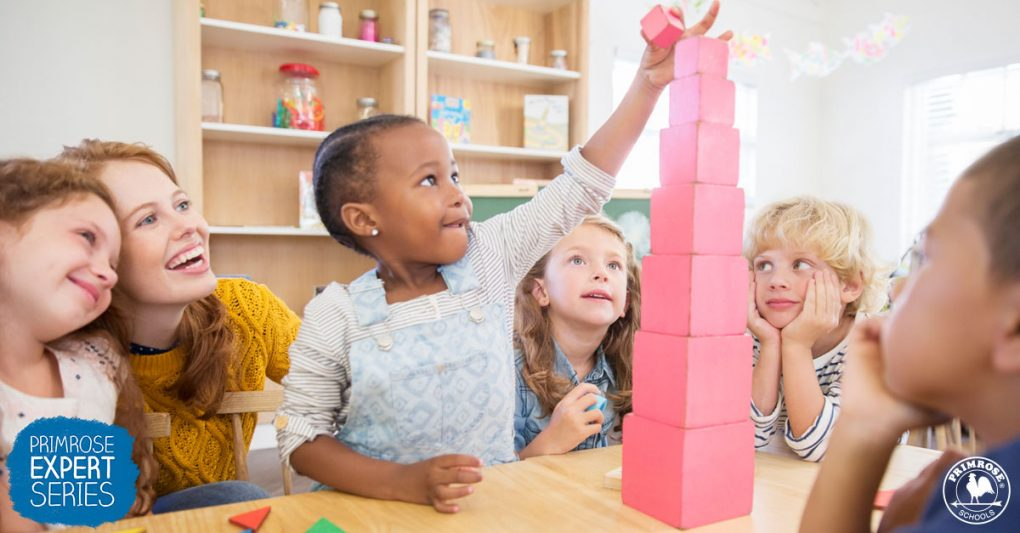 Young girl places final block on the block tower as her friends and teacher look on encouragingly
