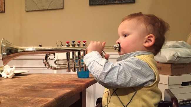 A little toddler boy plays a trumpet
