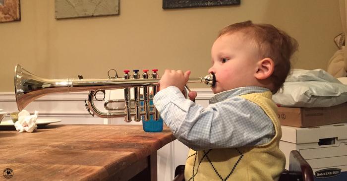 A little toddler boy plays a trumpet