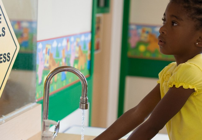 A primrose student washes her hands before meal time