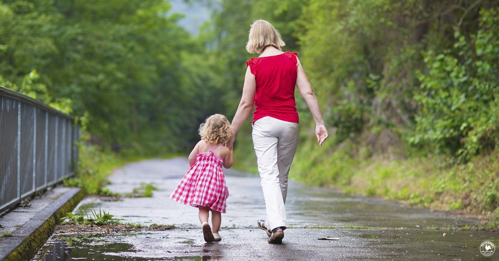 Mother and little toddler girl walking together in a park on a lovely day after rain