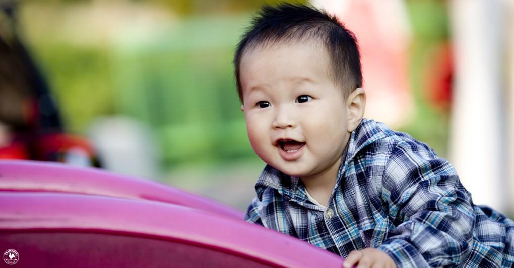 A toddler boy enjoying himself on a slide in the park
