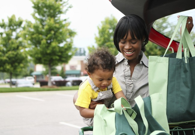 A toddler curiously peeks into a grocery bag as his mother puts them in the trunk of their car