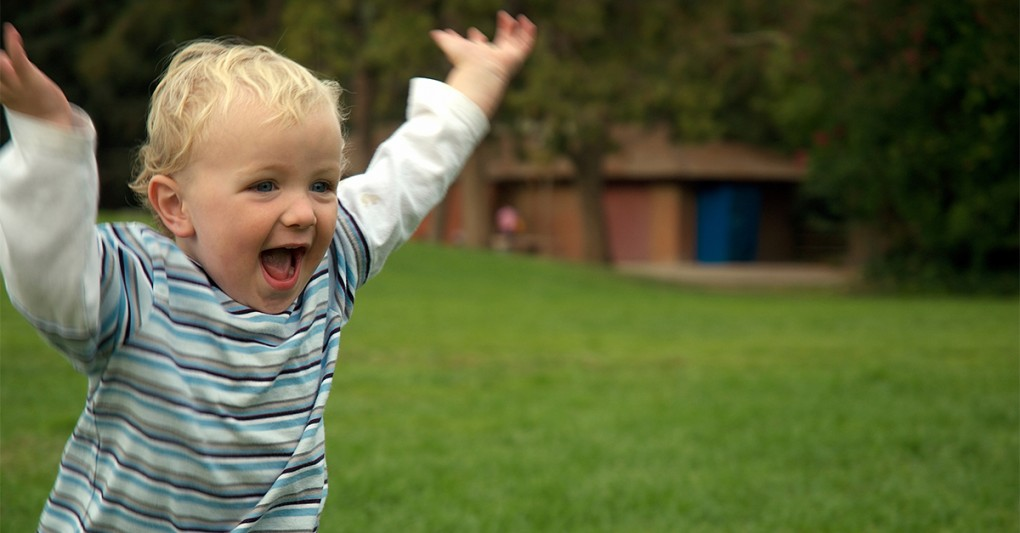 A happy toddler running outdoors