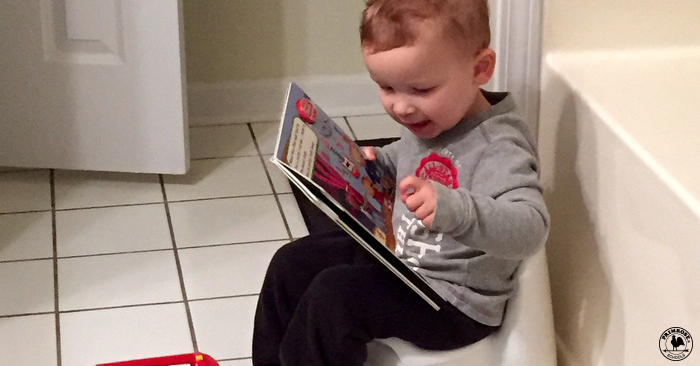 A little boy sitting on a potty in the bathroom, excitedly reading a storybook