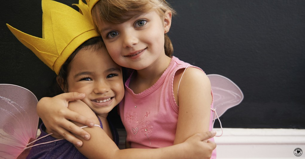 Two little girls dressed up as fairies hug each other
