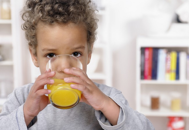 A little boy drinking a glass of orange juice