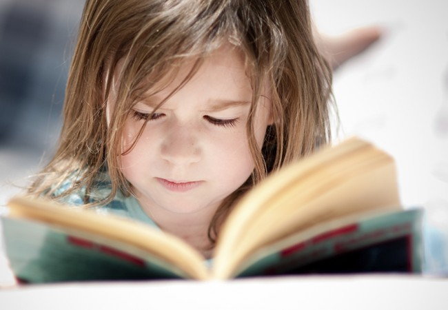 A young girl intently reads a book