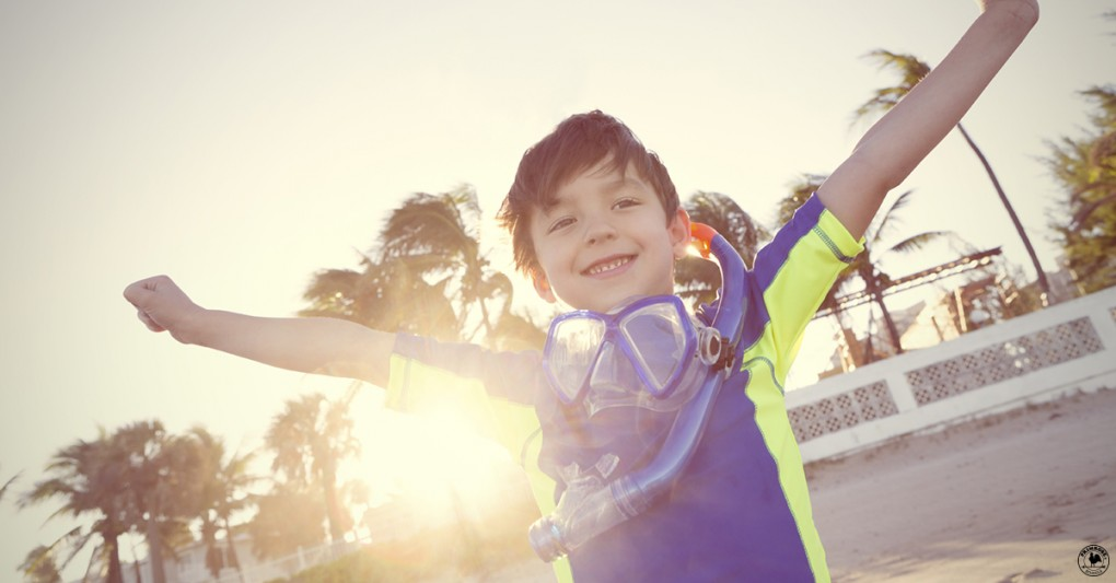 A young boy, wearing a scuba diving outfit, throws his arms up happily at the beach