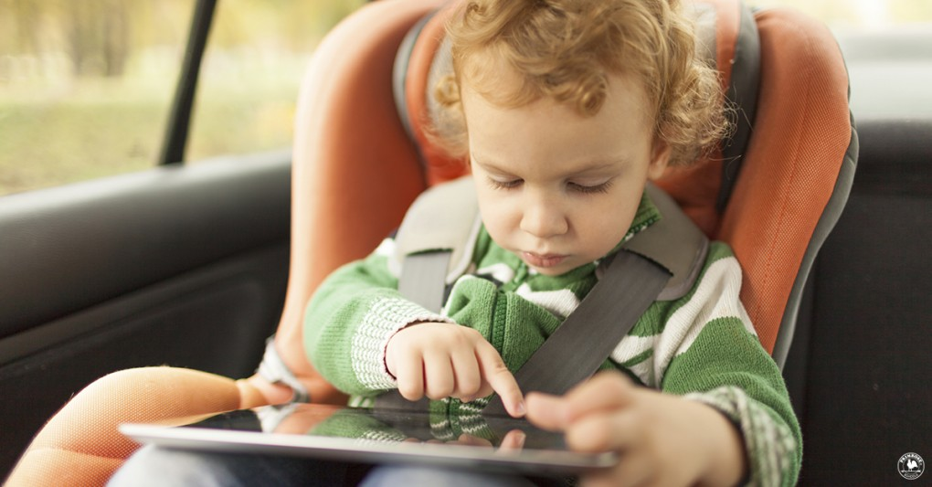 A curios little boy plays with a tablet