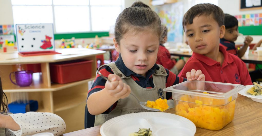 Two Primrose students scoop fruit out of bowl onto plate in preschool classroom