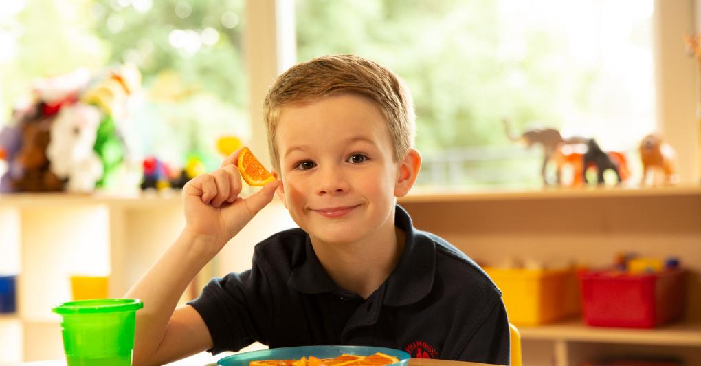 Boy smiling holding an orange