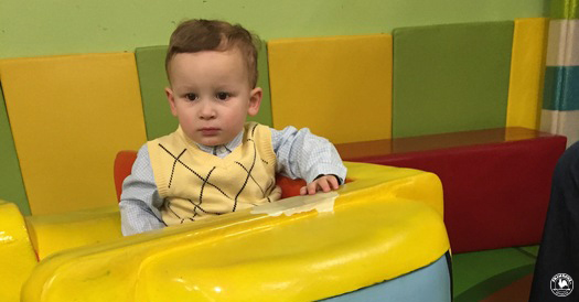 A toddler sits grumpily at a day care center