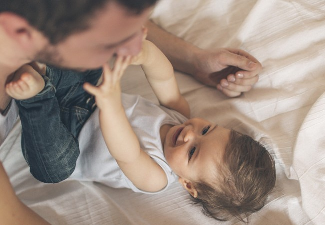 Toddler playfully reaches out to his father while they play on the bed