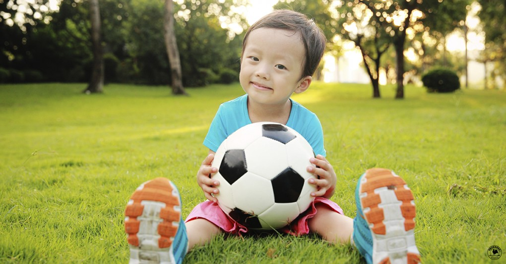 Little boy happily holding a soccer ball, sitting in a field