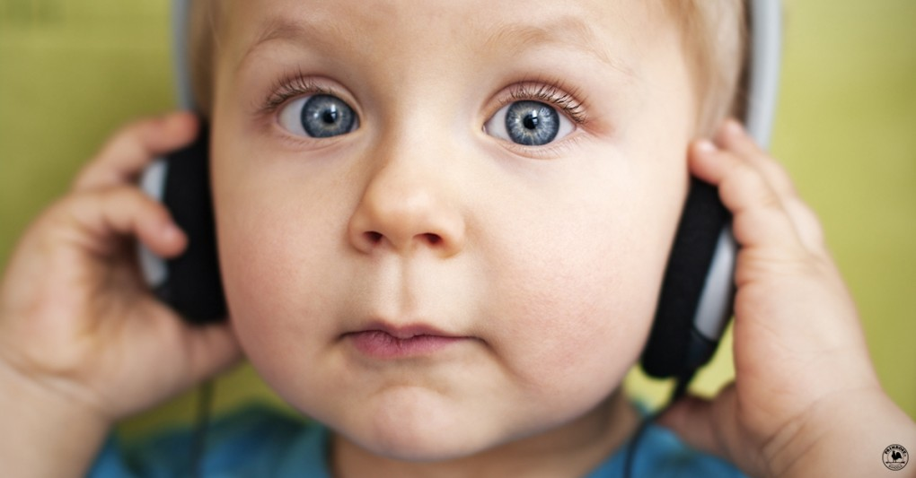 Little boy looks surprised as he listens to music on a pair of headphones