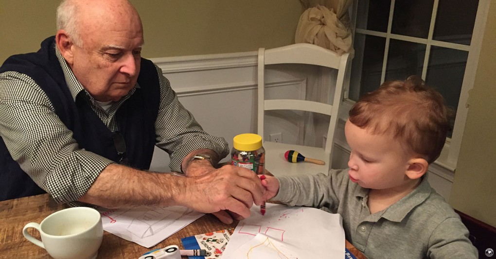Reminiscent of the old days, a grandfather helps his grandson color while babysitting him
