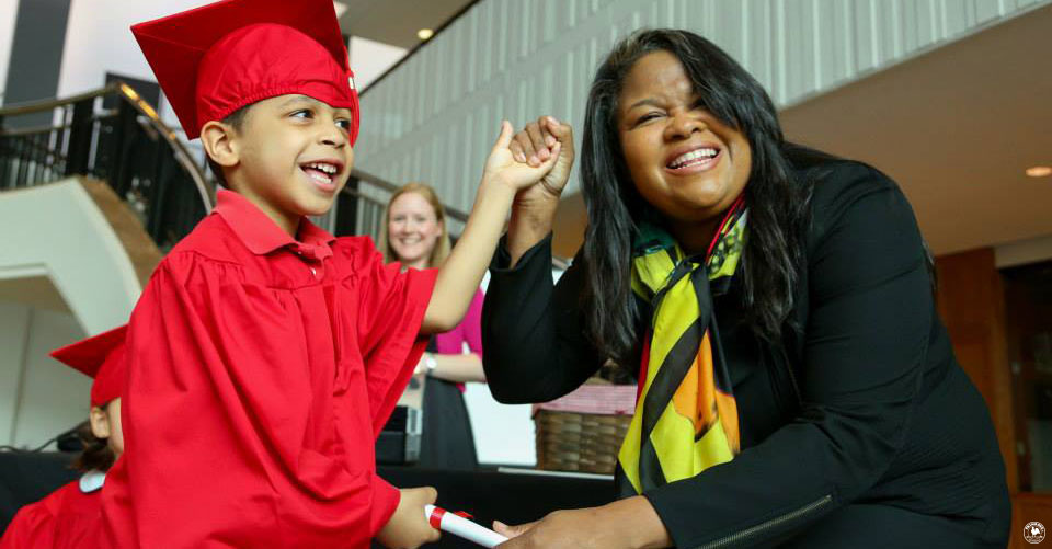 A mother smiles ecstatically as her little son graduates from Primrose school
