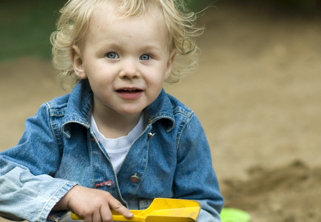 Little girl playing happily in a sand box