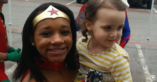 Happy young girl poses with a lady dressed as Wonderwoman