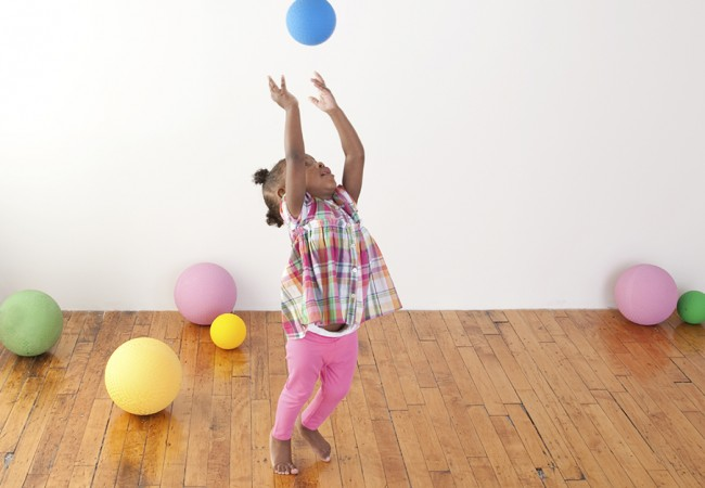 A little girl throws up a ball in the air in a playroom