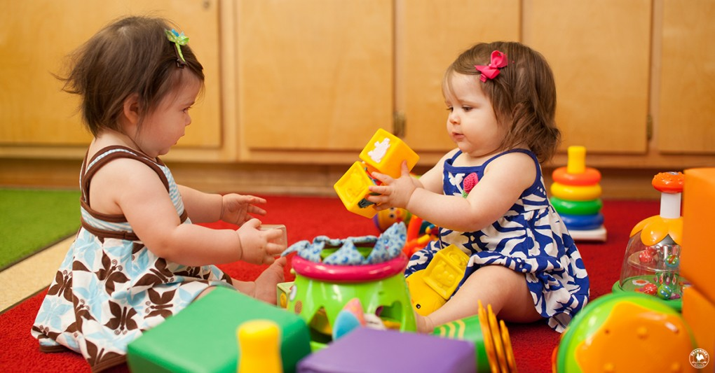 Two little toddler girls, surrounded by different toys, play with blocks at a day care center
