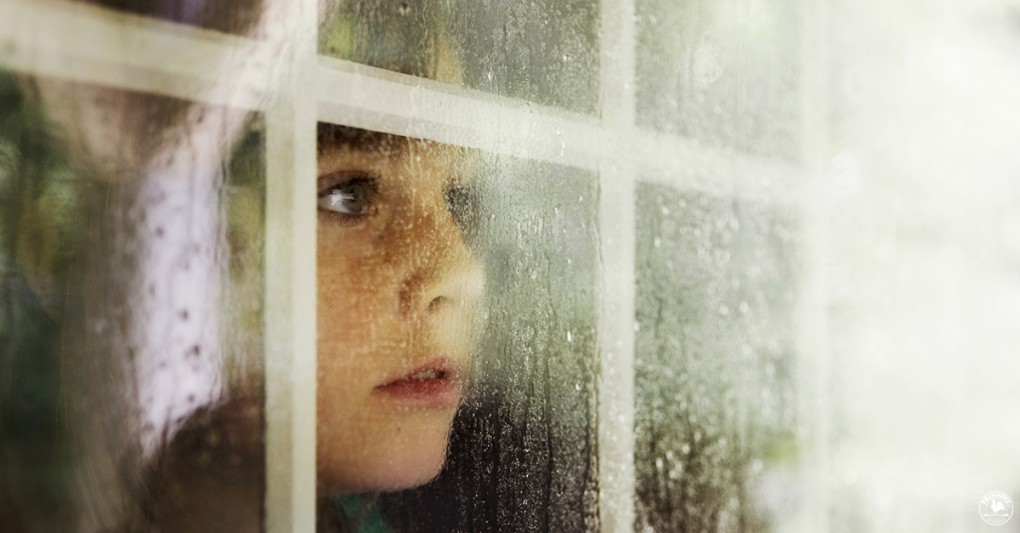 A little girl gazes out the window during heavy rains
