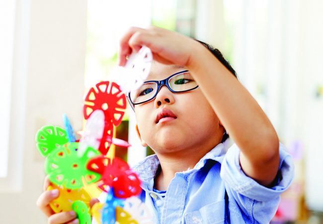 Young child building a structure with colorful discs
