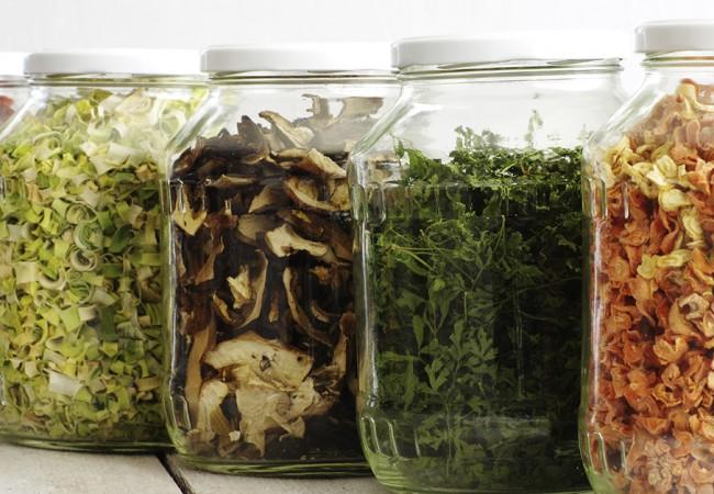 Berries, vegetables, mushrooms and herbs, neatly placed in separate jars