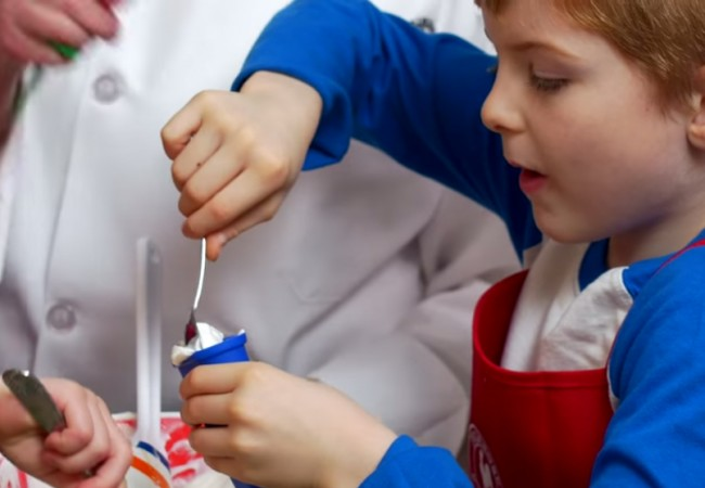 A young Primrose student fills yogurt into a popsicle mold