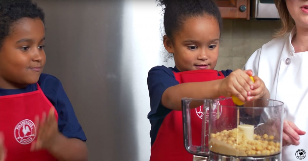 Little girl squeezing lemon juice into a food processor full of chickpeas to make hummus