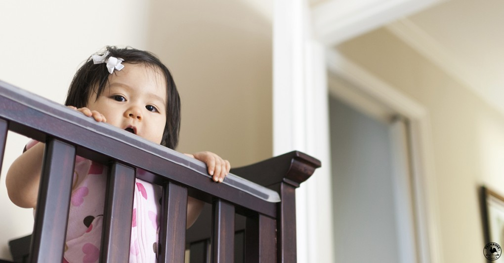 An adorable little girl stands inside her baby crib and peers out over the railing.