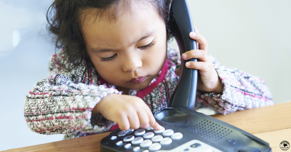 A little girl practices dialing a number in case of an emergency