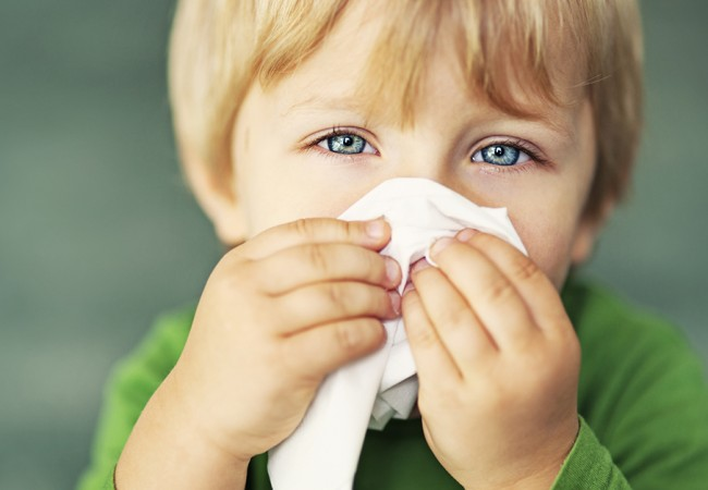 A little boy holds a napkin over his nose
