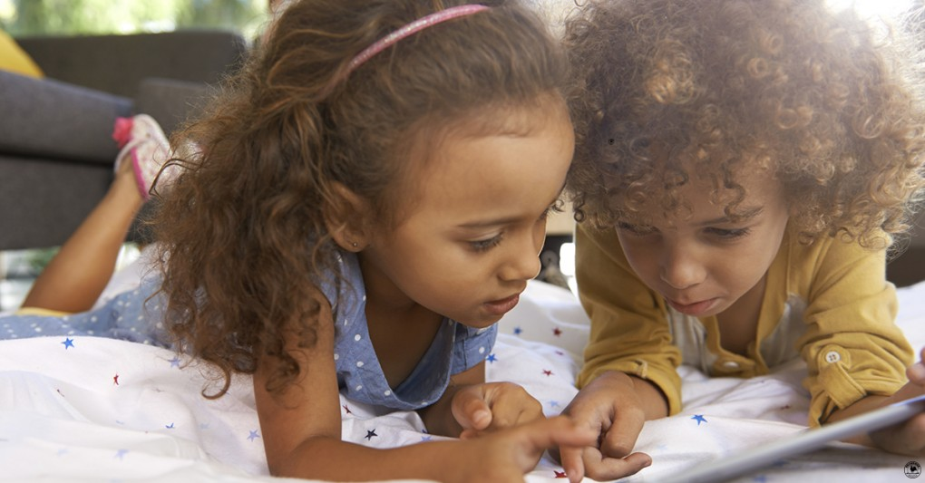 Two young girls play with a tablet on the living room floor