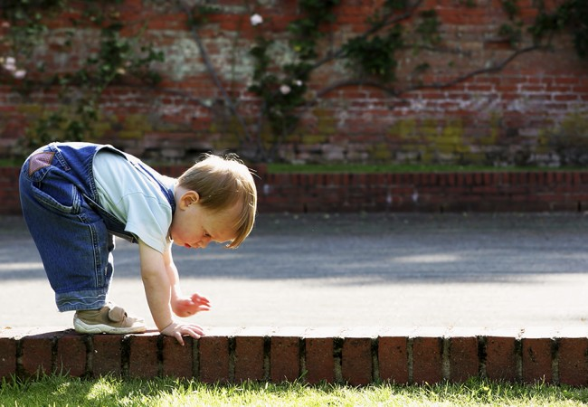 A little toddler boy tries to balance himself by putting his hands and feet on the ground