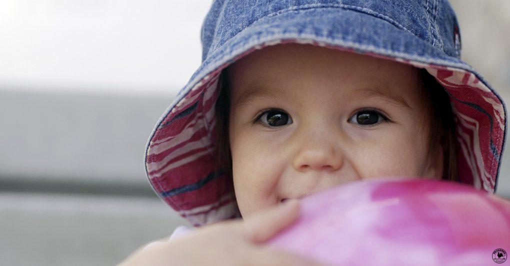 A little girl in a hat hugs a ball