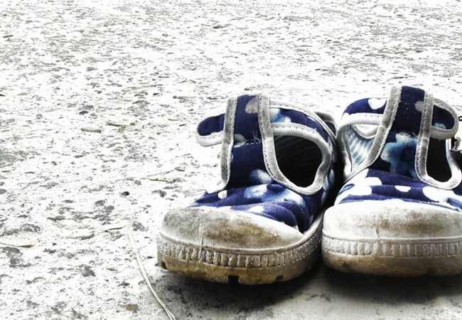 A pair of grimy toddler shoes, depicting the threat that was posed to children during hurricane Katrina