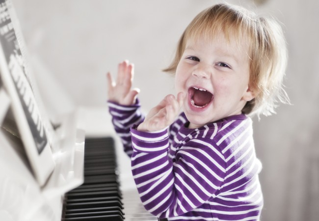 A young child laughs happily as he sits by the piano