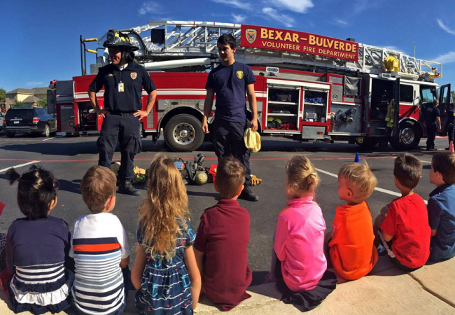 Primrose students interacting with firefighters at an outdoor safety demonstration