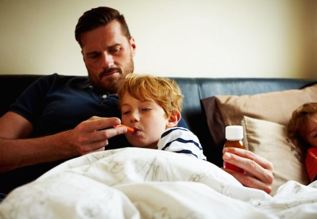 Dad checks for flu symptoms by measuring temperature of his sick son.