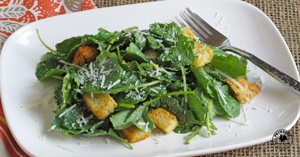 A salad make with kale and croutons, sprinkled with cheese