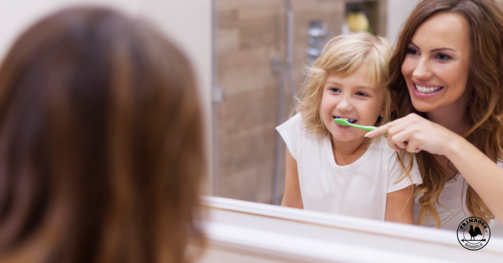 Mother helping her daughter brush her teeth