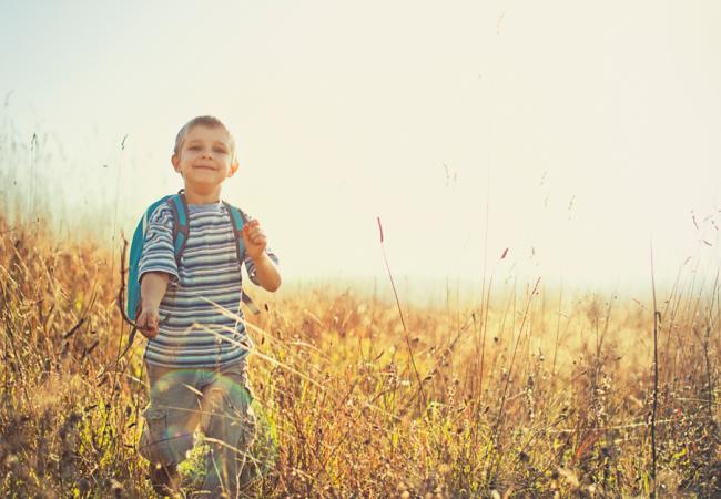 A happy boy explores an open field