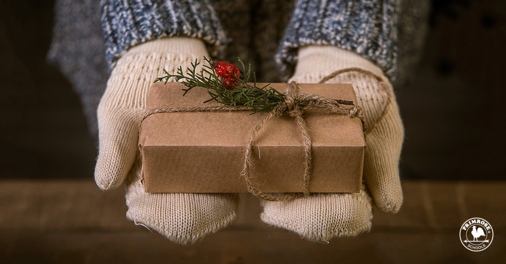 Close up of a little child's hands, wearing mittens and holding a simple and beautifully wrapped Christmas present