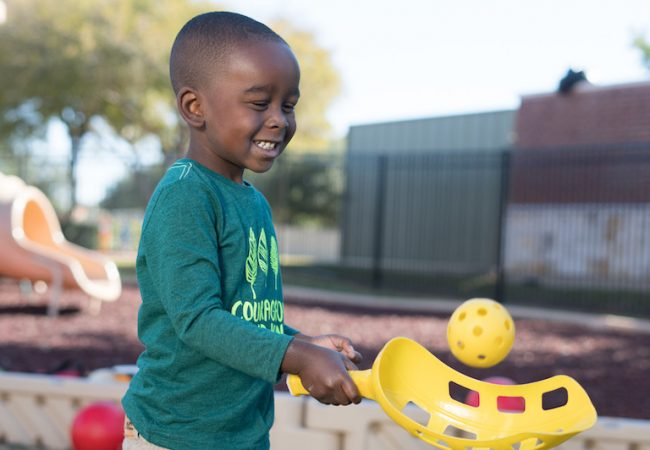 Little boy plays with scoop ball on Primrose playground